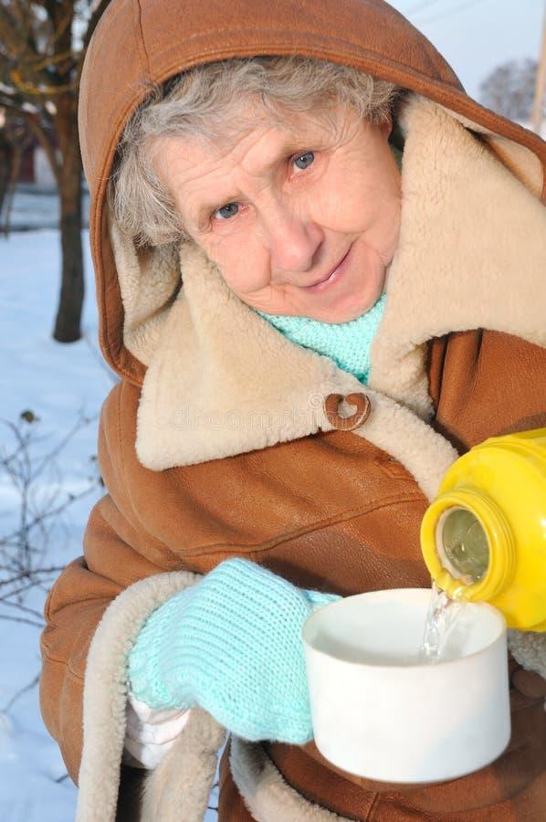 Avó feliz com o thermos no fundo do inverno foto de stock