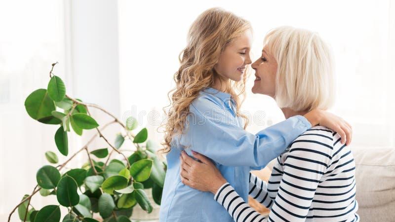 Avó feliz e neta que tocam nos narizes em casa foto de stock royalty free
