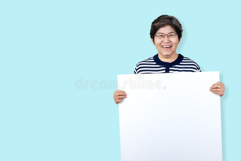A avó feliz que sorri com dentes brancos, aprecia o momento e guardar uma placa vazia Mulher mais idosa asiática que mostra a pla imagem de stock royalty free