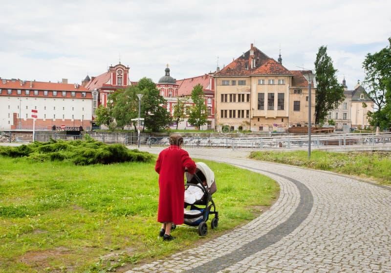 Avó idosa que anda com o bebê no carrinho de criança fotos de stock royalty free