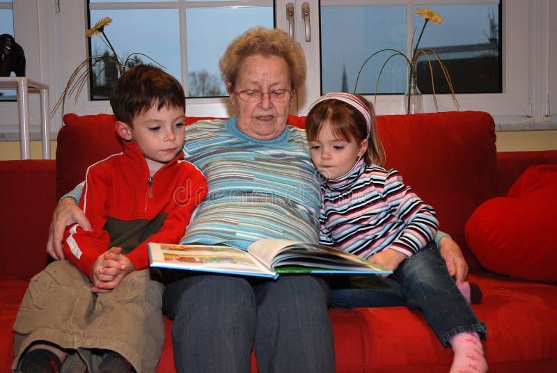 A avó lê alto com seus netos fotos de stock