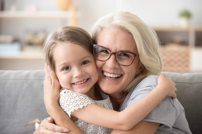 Avó mais idosa feliz que abraça pouca menina do neto que olha a fotos de stock royalty free