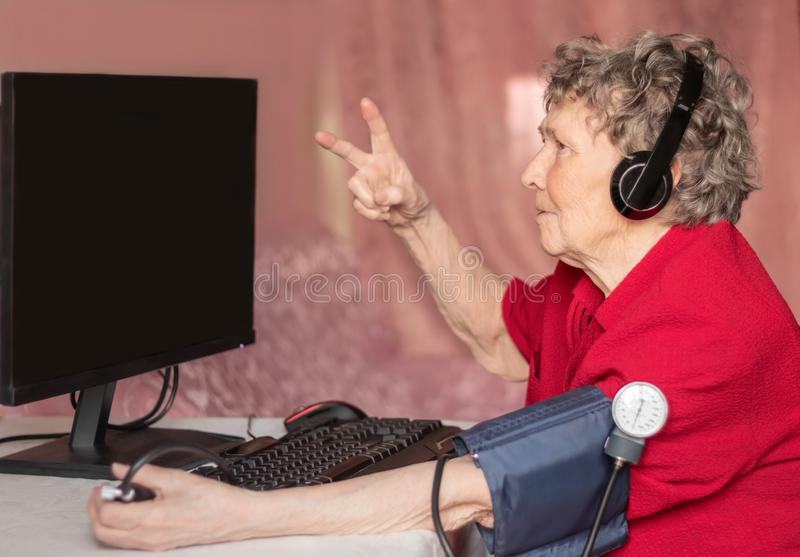 Avó no mundo moderno do de alta tecnologia As avó amam jogos de computador foto de stock royalty free