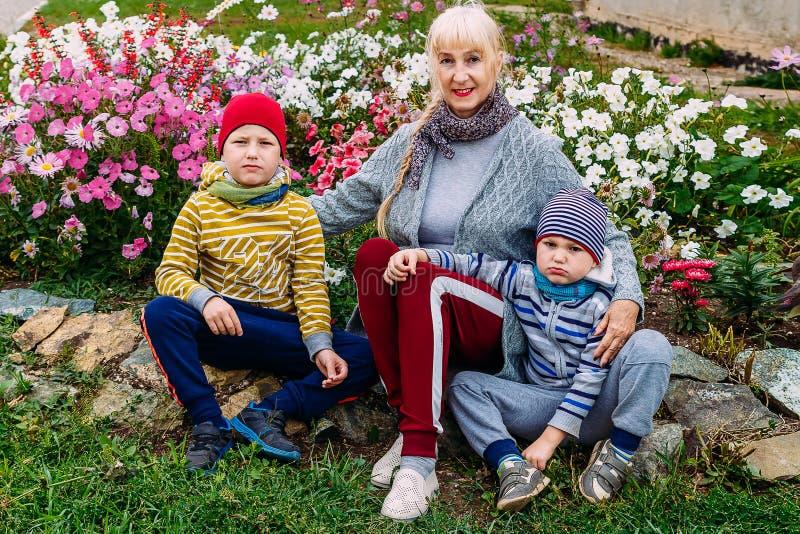 A avó nova abraça dois netos fotografia de stock
