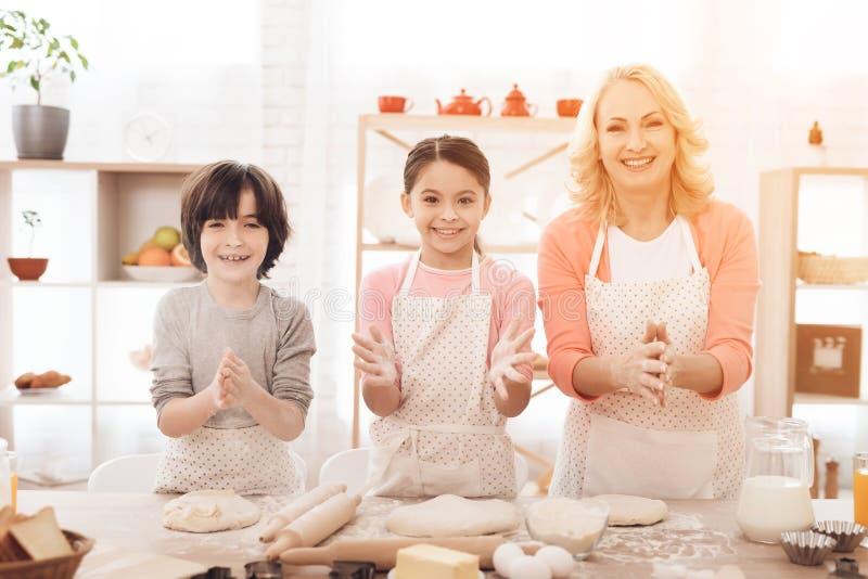 A avó nova com netos pequenos está rindo na cozinha Cookies do cozimento fotos de stock royalty free