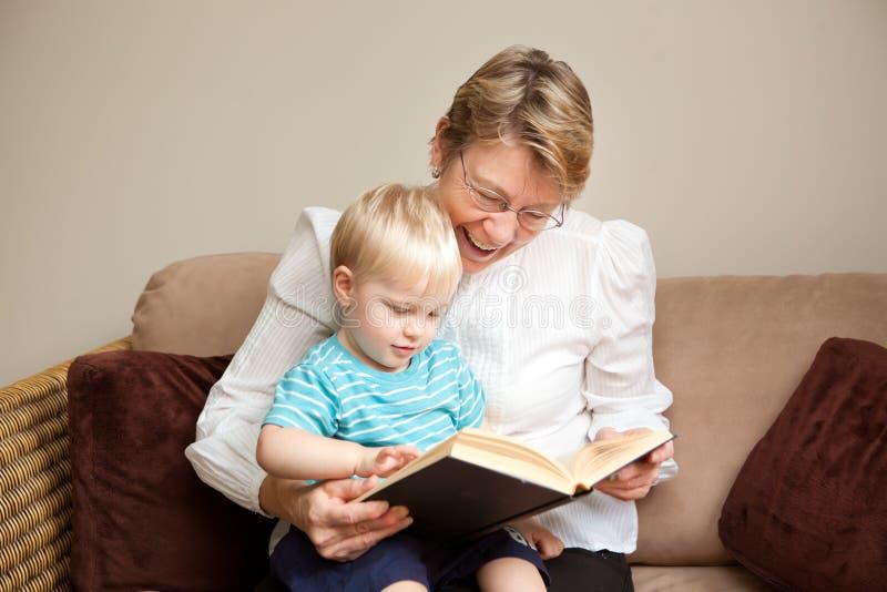 Avó ou baby-sitter que lêem a uma criança fotografia de stock