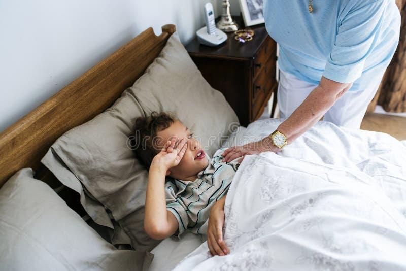 Avó que acorda seu neto acima da cama fotografia de stock