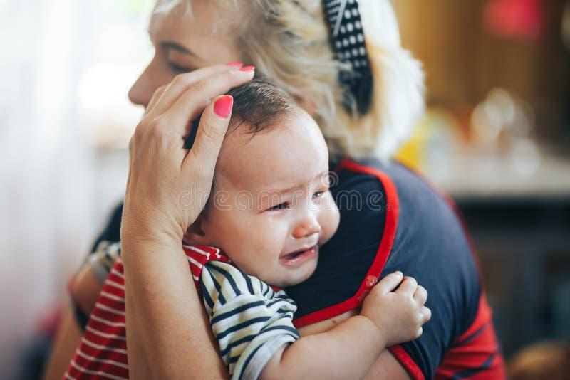 Avó que embala o bebê infantil de grito que olha a câmera fotos de stock