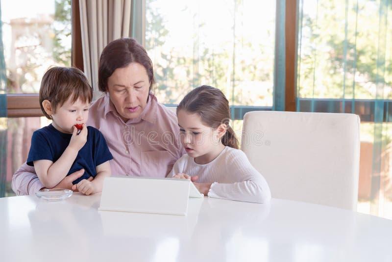 Avó que mante distraído seus netos pequenos com um jogo de tablet pc foto de stock