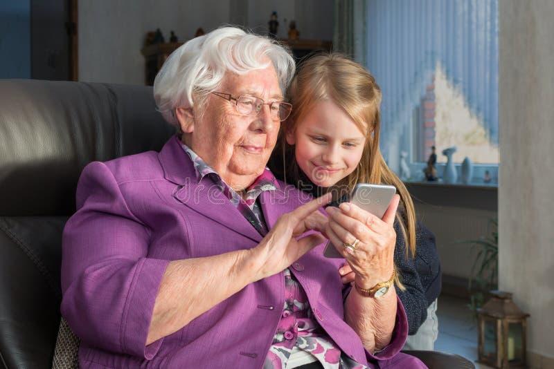 Avó que mostra a seu neto algo engraçado em seu smartp imagem de stock