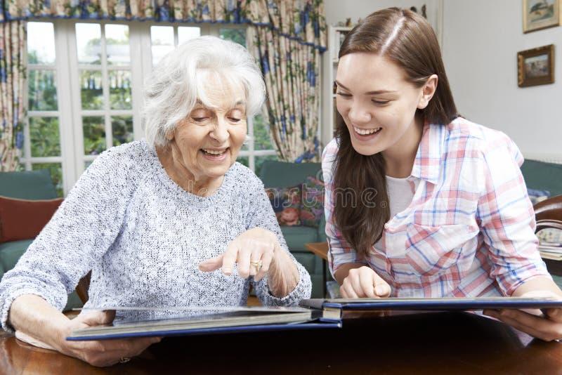 Avó que olha o álbum de fotografias com neta adolescente imagem de stock