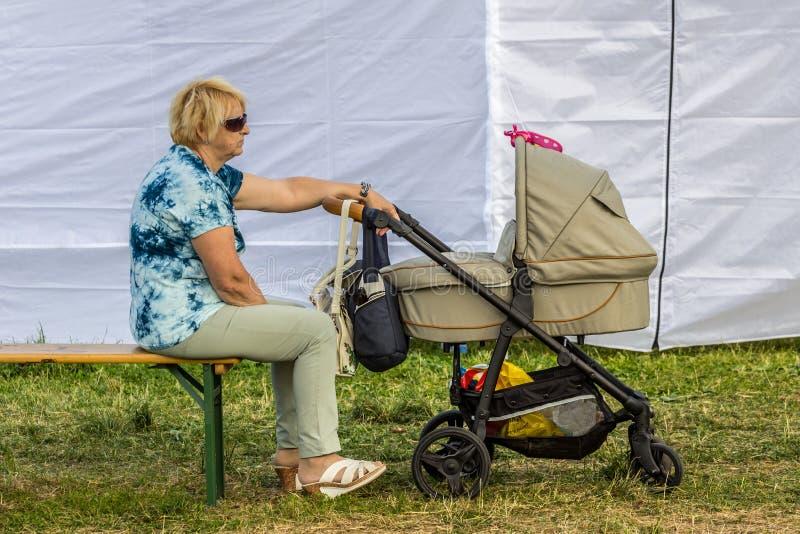 Avó que senta-se no banco no parque e que agita o carrinho de criança com bebê de sono imagens de stock