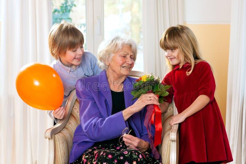 A avó recebe flores das crianças grandes fotografia de stock