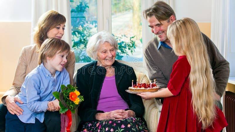 A avó recebe flores das crianças grandes fotos de stock