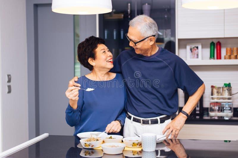 Avós asiáticas superiores dos pares que cozinham junto quando a mulher alimentar o alimento ao homem na cozinha foto de stock
