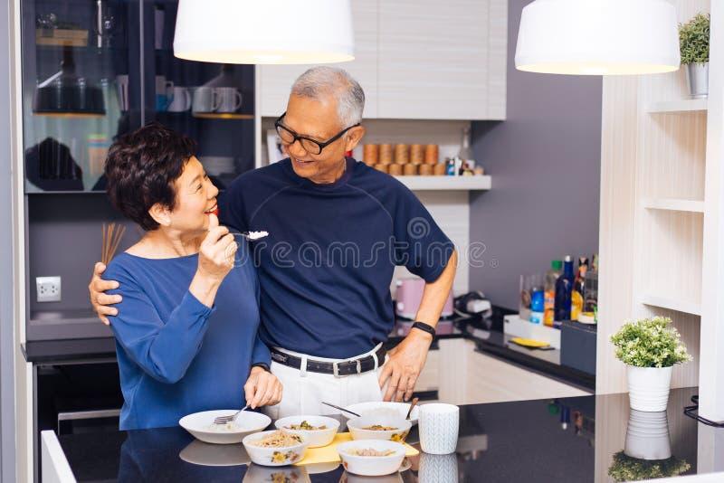 Avós asiáticas superiores dos pares que cozinham junto quando a mulher alimentar o alimento ao homem na cozinha Relacionamento du imagem de stock