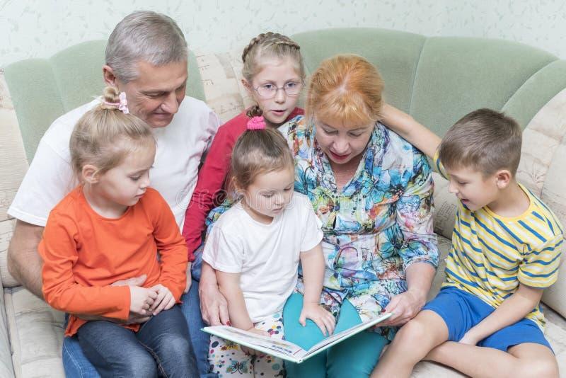 Avós com os netos no sofá imagem de stock