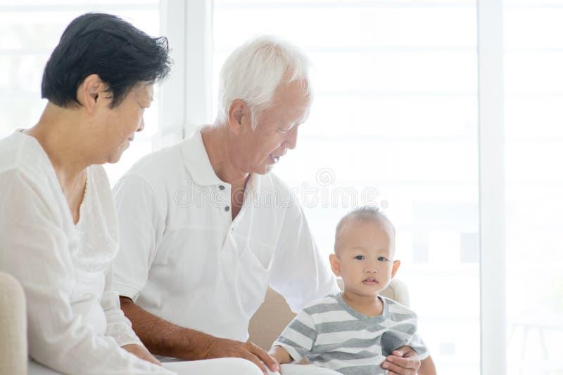 Avós e neto em casa fotos de stock