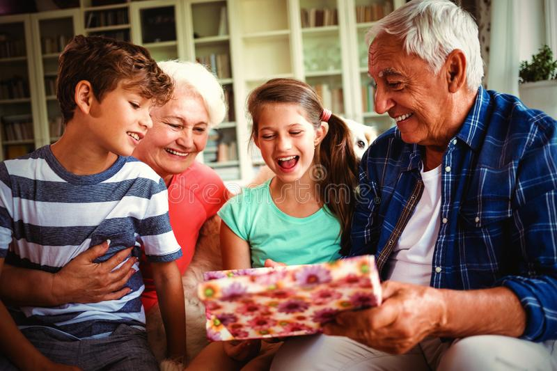 Avós e netos que olham o presente da surpresa na sala de visitas imagem de stock