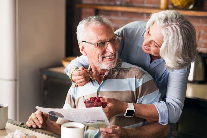 Avós felizes que têm negociações e risos ao comer na cozinha fotos de stock