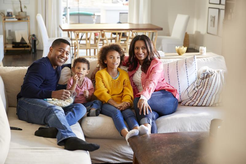 Avós novas que sentam-se com seus netos no sofá na sala de visitas que olham a tevê, foco seletivo fotografia de stock royalty free