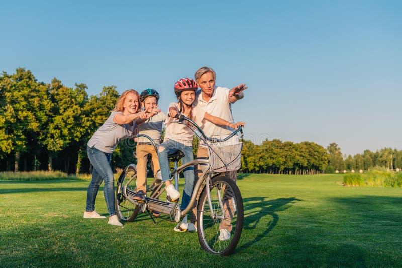 Avós que ajudam a bicicleta do passeio das crianças fotografia de stock