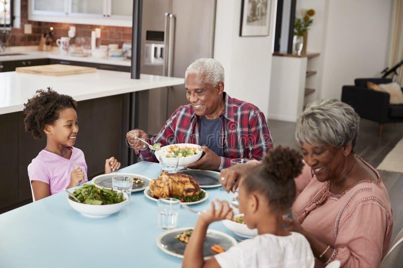 Avós que apreciam a refeição em casa com netas foto de stock