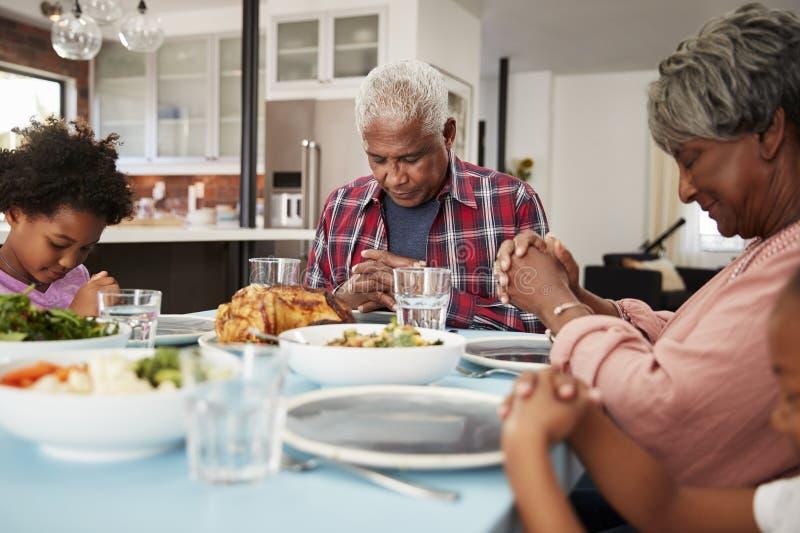Avós que rezam antes da refeição em casa com netas fotos de stock royalty free
