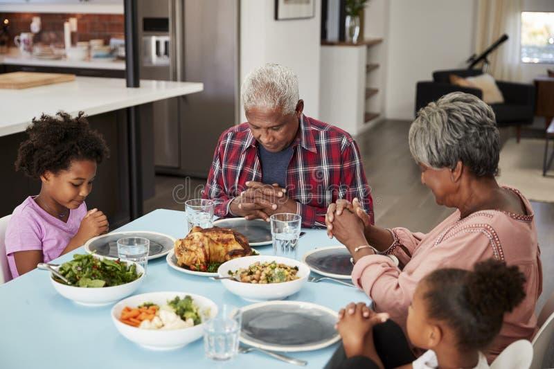 Avós que rezam antes da refeição em casa com netas fotos de stock