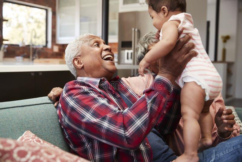 Avós que sentam-se em Sofa Playing With Baby Granddaughter em casa imagem de stock royalty free