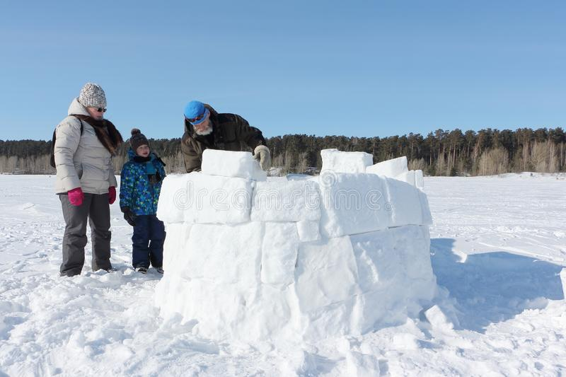 Avô, avó feliz e neto construindo um iglu em uma clareira nevado no inverno imagem de stock