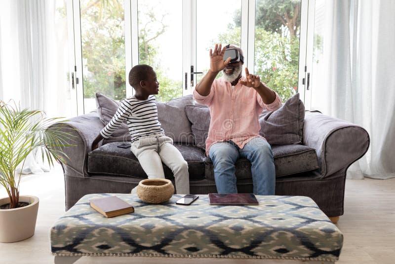 Avô com o neto que usa auriculares da realidade virtual na sala de visitas fotos de stock royalty free