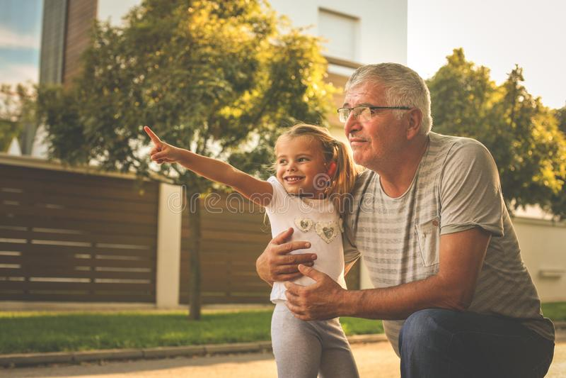 Avô com sua neta na rua que olha algo nádegas imagem de stock royalty free