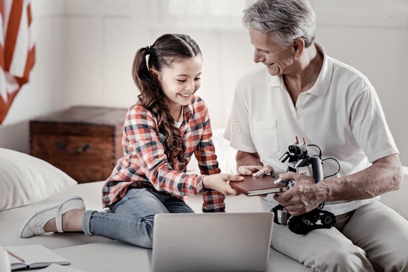 Avô considerável loving e neta pequena que têm o divertimento com robô fotografia de stock