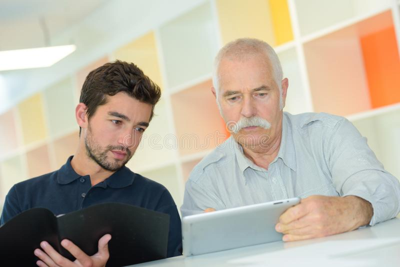 Avô de ensino do neto para usar a tabuleta digital fotos de stock