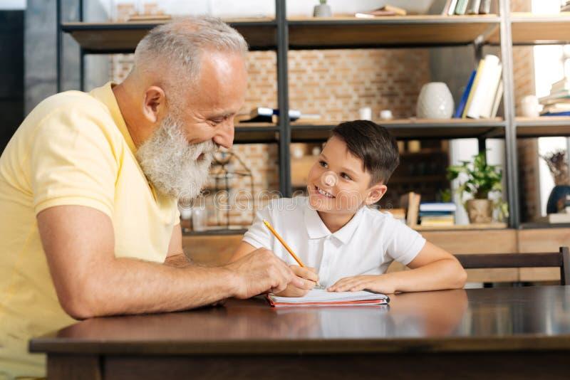 Avô de inquietação que dá pontas na atribuição dos netos em casa foto de stock royalty free
