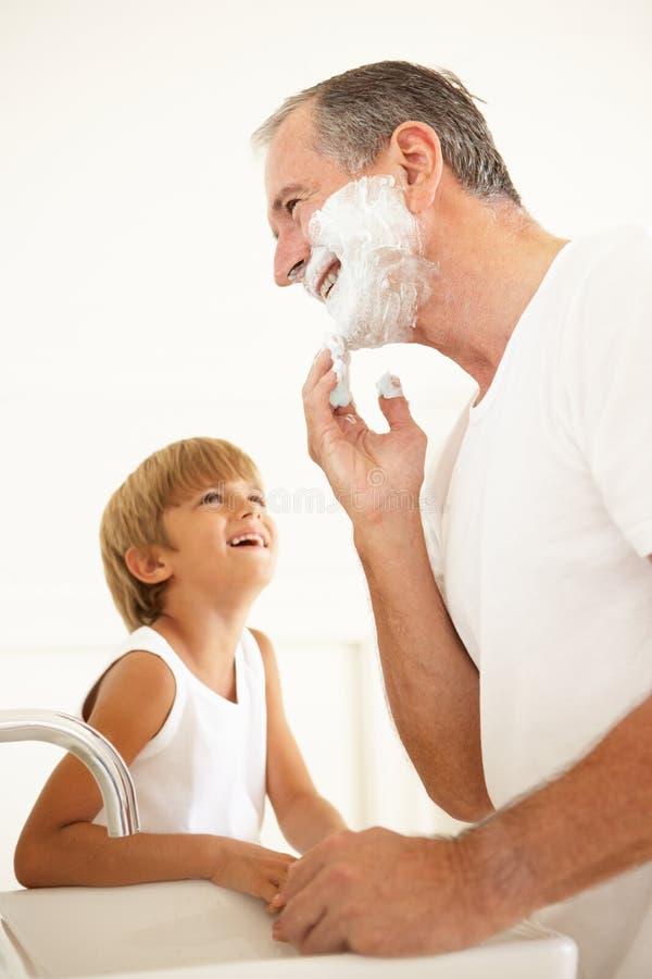 Avô de observação do neto que raspa no banheiro fotografia de stock