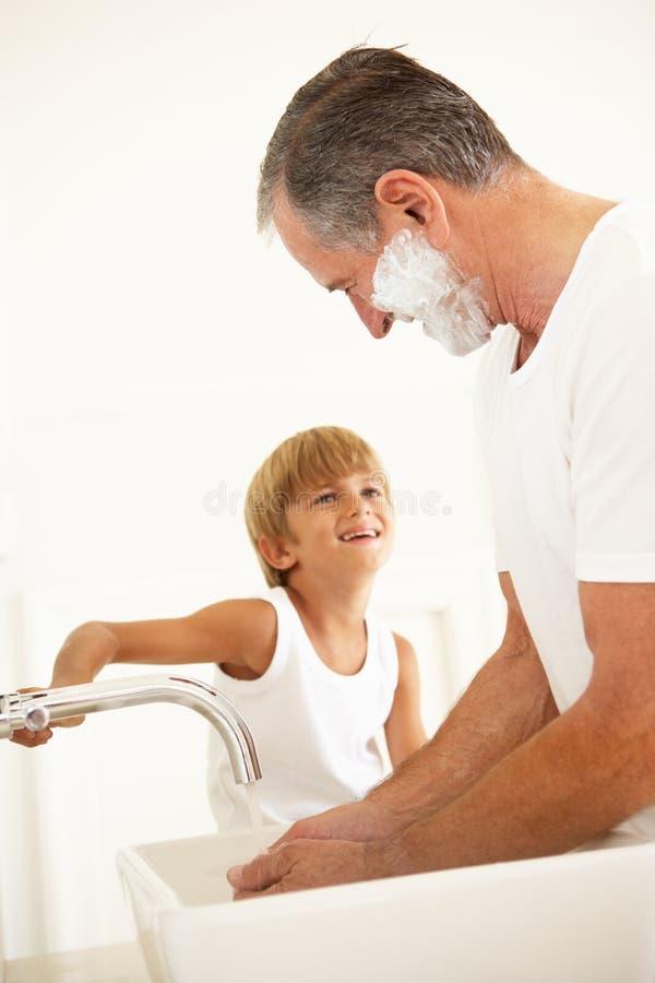 Avô de observação do neto que raspa no banheiro imagens de stock royalty free