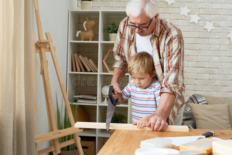 Avô e Little Boy que trabalham com madeira fotografia de stock