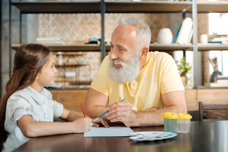 Avô e neta de sorriso que pintam uma imagem junto imagem de stock