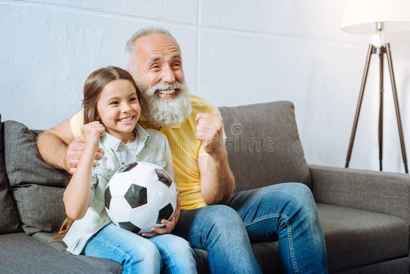 Avô e neta que comemoram o objetivo da equipe favorita fotografia de stock royalty free