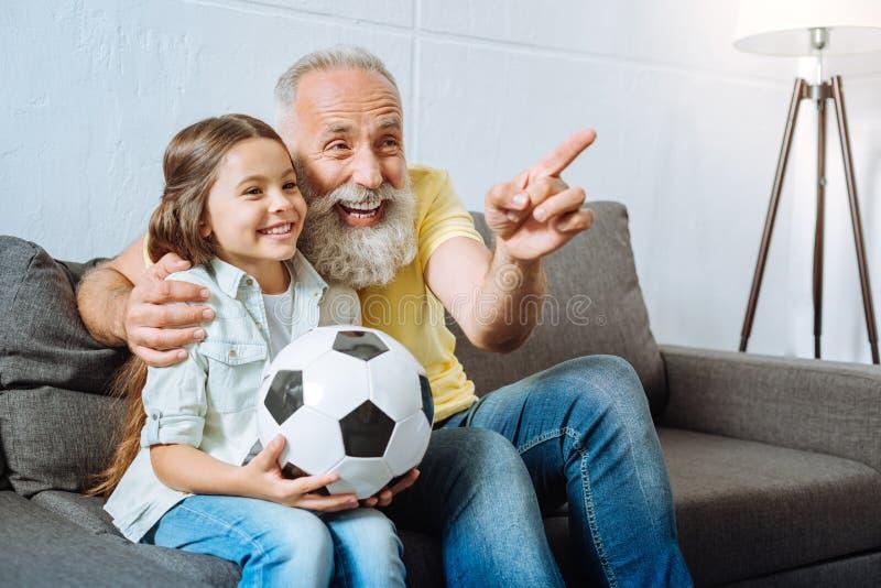 Avô e neta que riem do momento engraçado durante o futebol imagem de stock royalty free