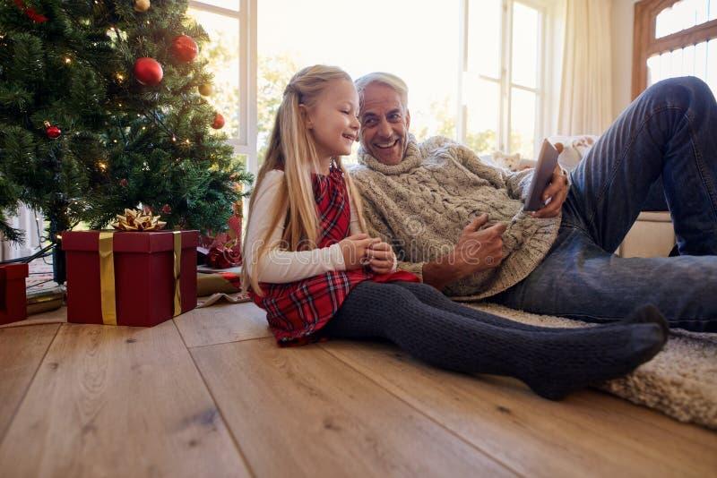 Avô e neta que usa o durin digital da tabuleta em casa fotos de stock