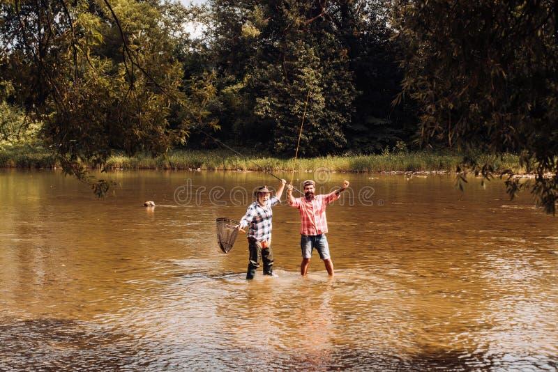 Avô e neto felizes com as varas de pesca no beliche do rio Pescadores com a vara de pesca no rio Pai feliz imagens de stock royalty free