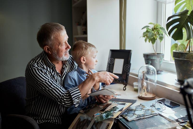 Avô e neto no sofá em casa Vovô e crianças que olham fotos velhas imagem de stock