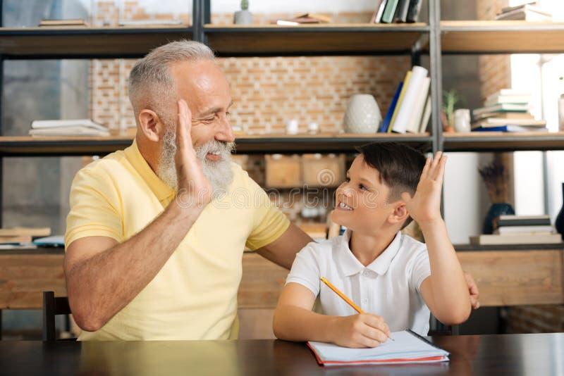 Avô e neto que dão-se a elevação cinco fotos de stock royalty free