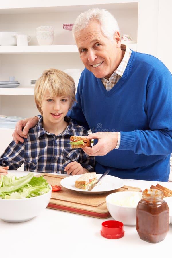Avô e neto que fazem o sanduíche imagens de stock royalty free