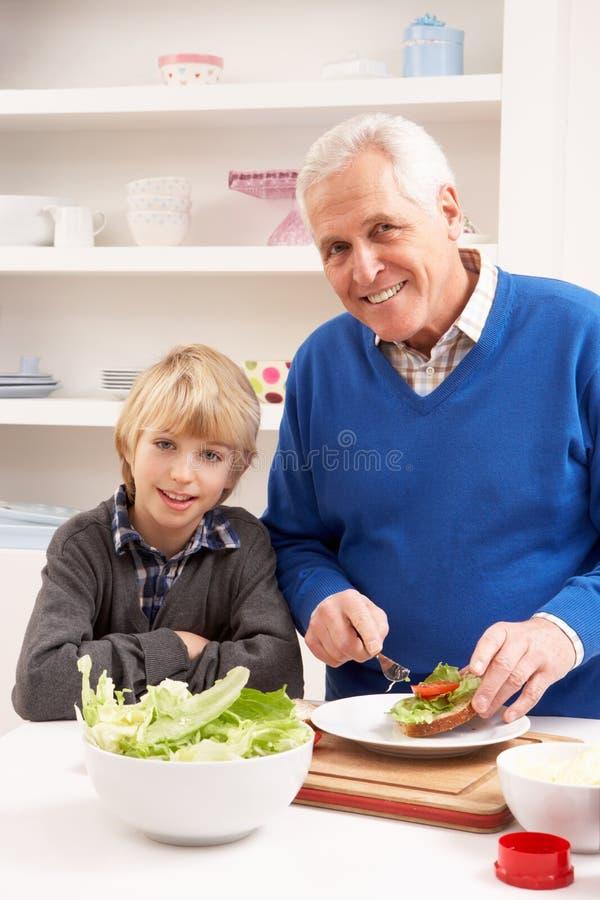 Avô e neto que fazem o sanduíche em Kitche imagens de stock royalty free