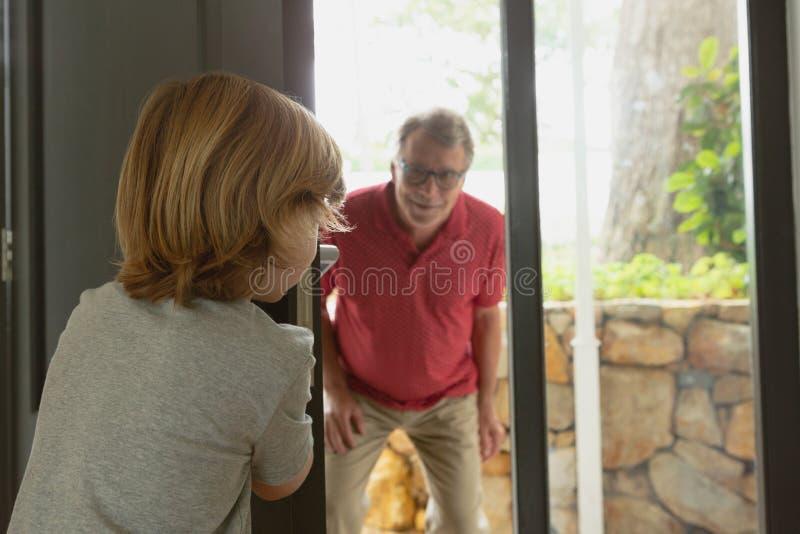 Avô e neto que jogam o esconde-esconde na casa confortável foto de stock royalty free