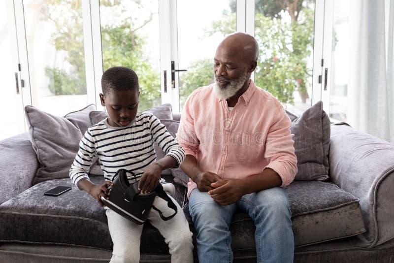 Avô e neto que sentam-se com os auriculares da realidade virtual na sala de visitas imagens de stock royalty free
